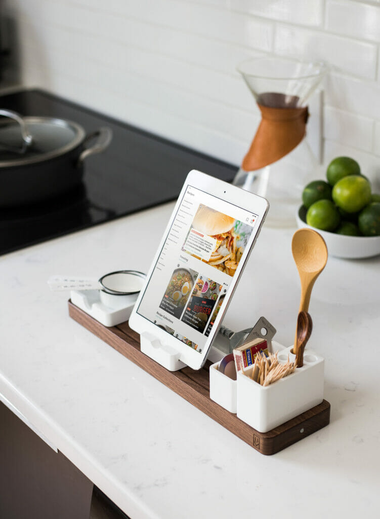 image shows kitchen scene with a tablet propped up with various kitchen utensils